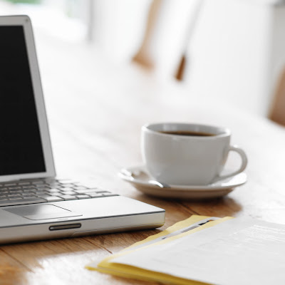 Laptop on Kitchen Table with Cup of Coffee --- Image by © Royalty-Free/Corbis